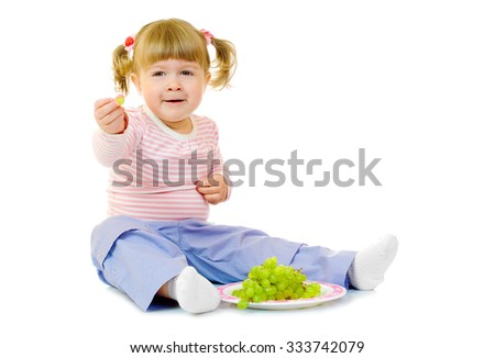 Little girl with grape isolated - stock photo