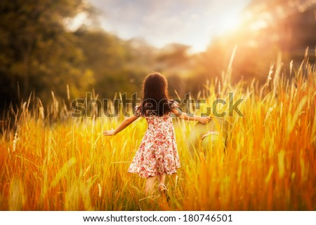 Little girl with green nature background and sunset - stock photo