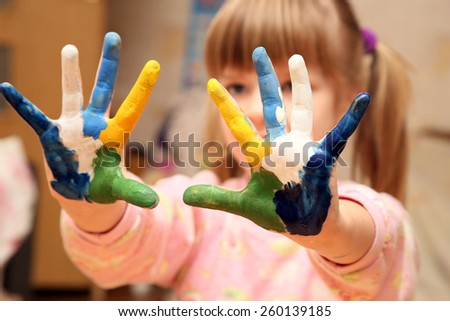 little girl with hands in paint  - stock photo
