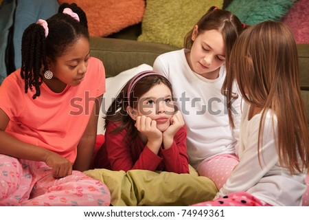Little girl with hands on chin at a pajama party - stock photo