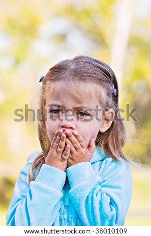 Little girl with hands over mouth and a look of shock or sadness. - stock photo