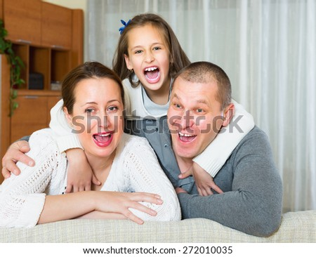 Little girl with happy parents posing at home and smiling - stock photo