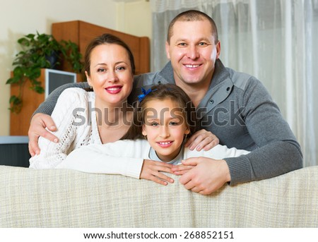 Little girl with happy parents posing in livingroom at home and smiling. Focus on girl - stock photo