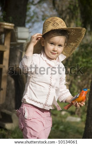 Little girl with hat in the garden