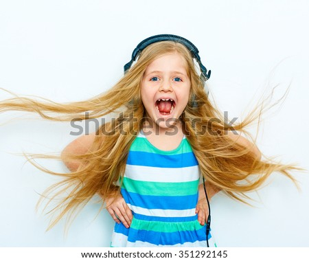 Little girl with headphones listen music and screams. Studio isolated portrait - stock photo