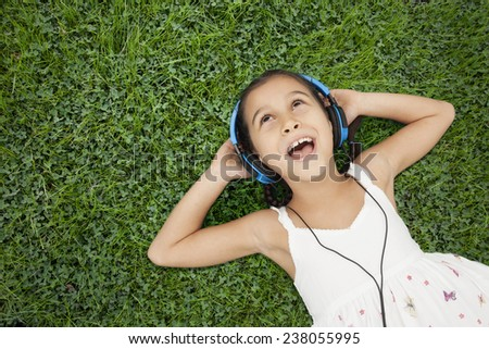 Little girl with headphones listening music