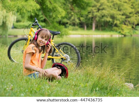 Little girl with headphones listening to music in summer park at lakeside. Girl resting after biking. - stock photo