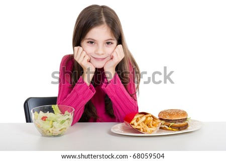 little girl with healthy and unhealthy food - stock photo