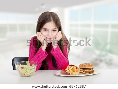 little girl with healthy and unhealthy food at home - stock photo