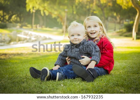 Little Girl with Her Baby Brother Wearing Winter Coats Outdoors Sitting at the Park.  - stock photo