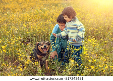 Little girl with her brother on the flower field with dog