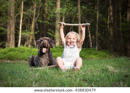 Little girl with her dog in the wood on a sunny day. Best friends concept.Outdoor activity and game with family pet on summer holiday.