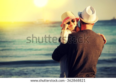 Little girl with her father   playing on the beach - stock photo