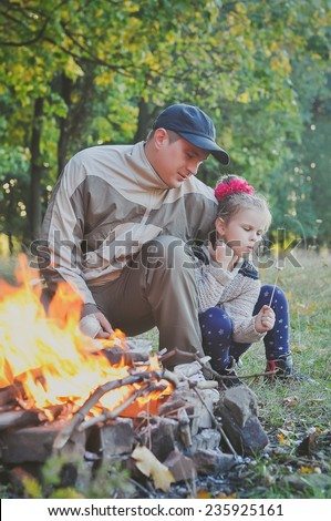 Little girl with her father roasting a marshmallow in the campfire - stock photo