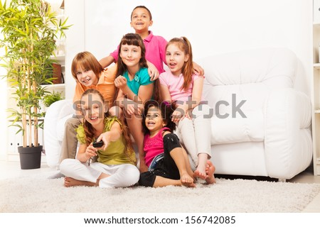 Little girl with her friends sitting on the sofa switch on TV with remote control - stock photo