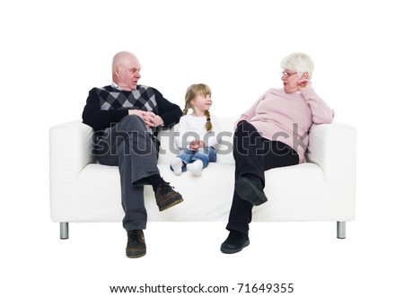 Little Girl with her grandparents in a sofa isolated on white background