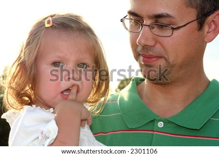 Little girl with her hand in her mouth and unsure expression, being held by her father. - stock photo