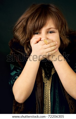 little girl with her hands over her mouth - stock photo