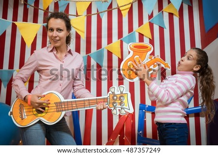Little girl with her mother are playing on guitar and saxophone near striped wall.