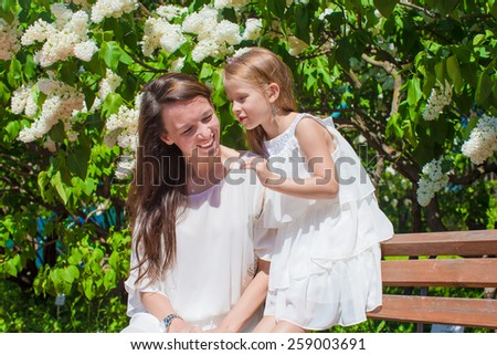 Little girl with her mother in the lush garden - stock photo