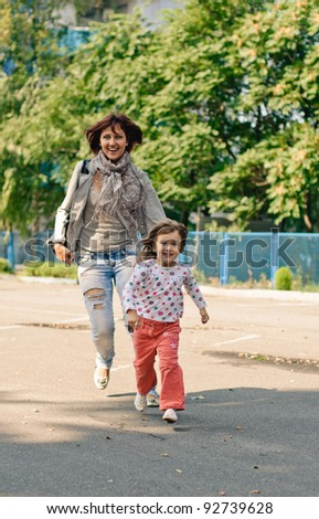 little girl with her mother in the park - stock photo