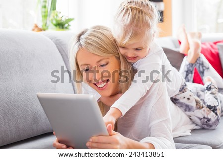 Little girl with her mother using tablet computer - stock photo