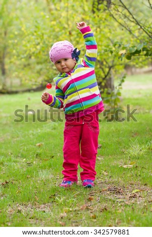 Little girl with his hand raised eating a lollipop outdoors. The composition of the forest. - stock photo