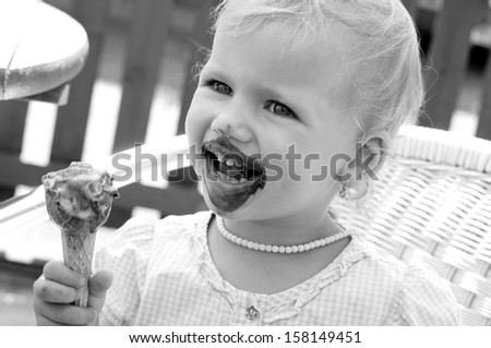 little girl with ice cream - black and white - stock photo