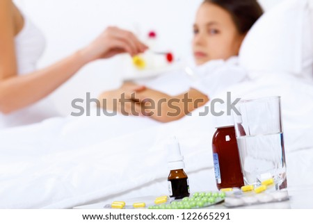 Little girl with illness at bed at home - stock photo