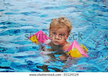 Little girl with inflatable over sleeves floats in pool - stock photo
