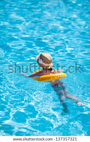 Little girl with inflatable ring at swimming pool