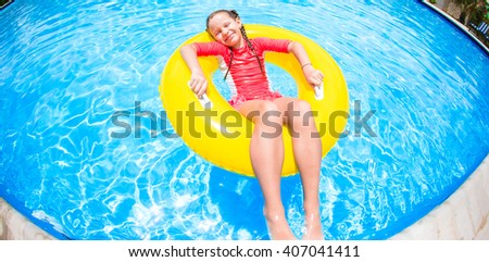 Little girl with inflatable rubber circle having fun in swimming pool - stock photo