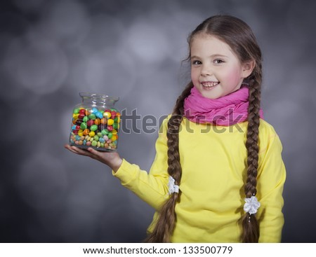 Little girl with jelly bean. Studio shot with a little noise - stock photo