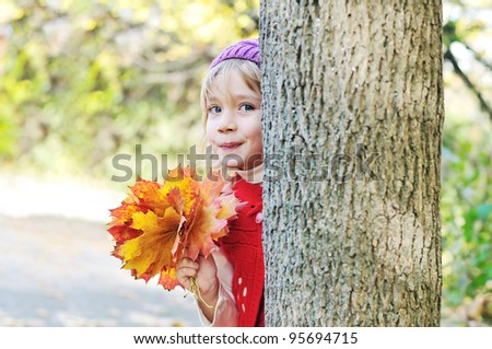 little girl with leaves in forest - Peekaboo! I see you! - stock photo