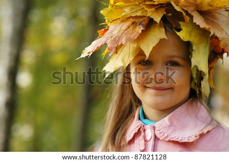 little girl with leaves on her head - stock photo