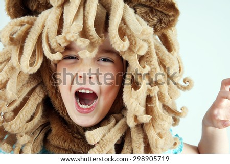 Little girl with lion mane costume roaring, playing