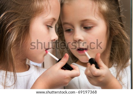 Little girl with lipstick at mirror