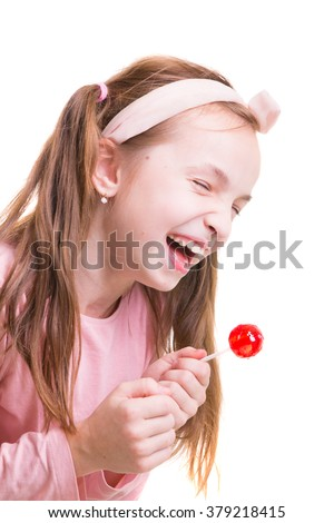 Little girl with lollipop is laughing. Shriek with laughter. Girl screw up her eyes (narrow her eye) with laughter. - stock photo