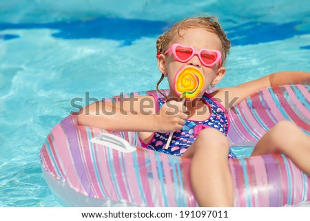 little girl with lollipop lying on the  inflatable rubber circle  in the swimming pool - stock photo