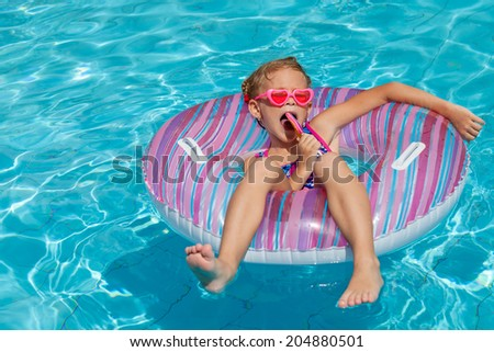 little girl with lollipop lying on the  inflatable rubber circle  in the swimming pool
