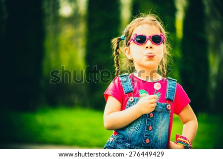 Little girl with lollipop outdoor in the park - stock photo