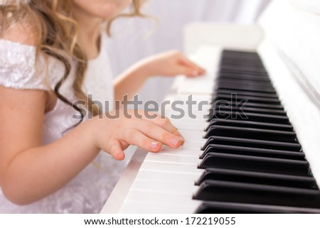 little girl with  long curls in white fashion dress playing on white piano, close-up - stock photo