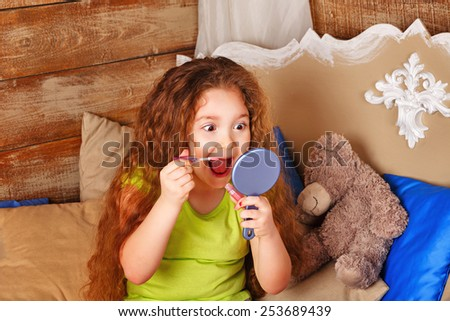 Little girl with long curly hair holds in hands mirror and lipgloss make-up and grimaces - stock photo