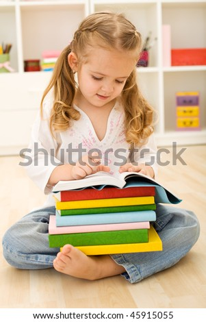 Little girl with lots of books sitting on the floor reading