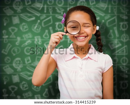 Little girl with magnifying glass against green chalkboard - stock photo