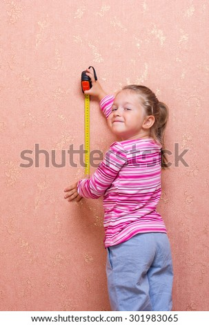Little girl with measure tape - stock photo