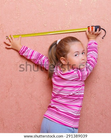 Little girl with measuring tape - stock photo