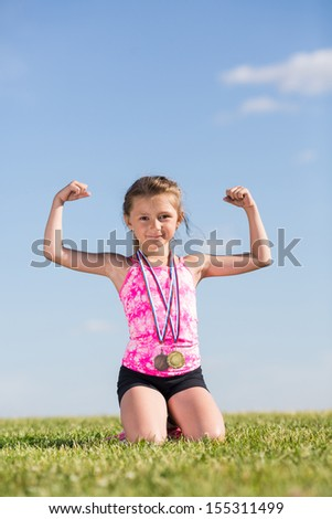 Little girl with medals sitting on the grass and demonstrates the strength