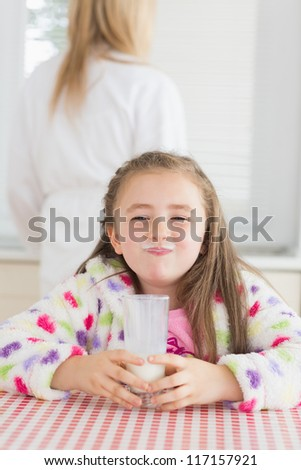 Little girl with milk moustache after drinking glass of milk - stock photo