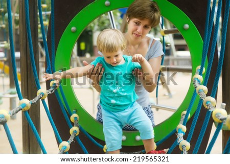 Little girl with mother at action-oriented playground in summer - stock photo